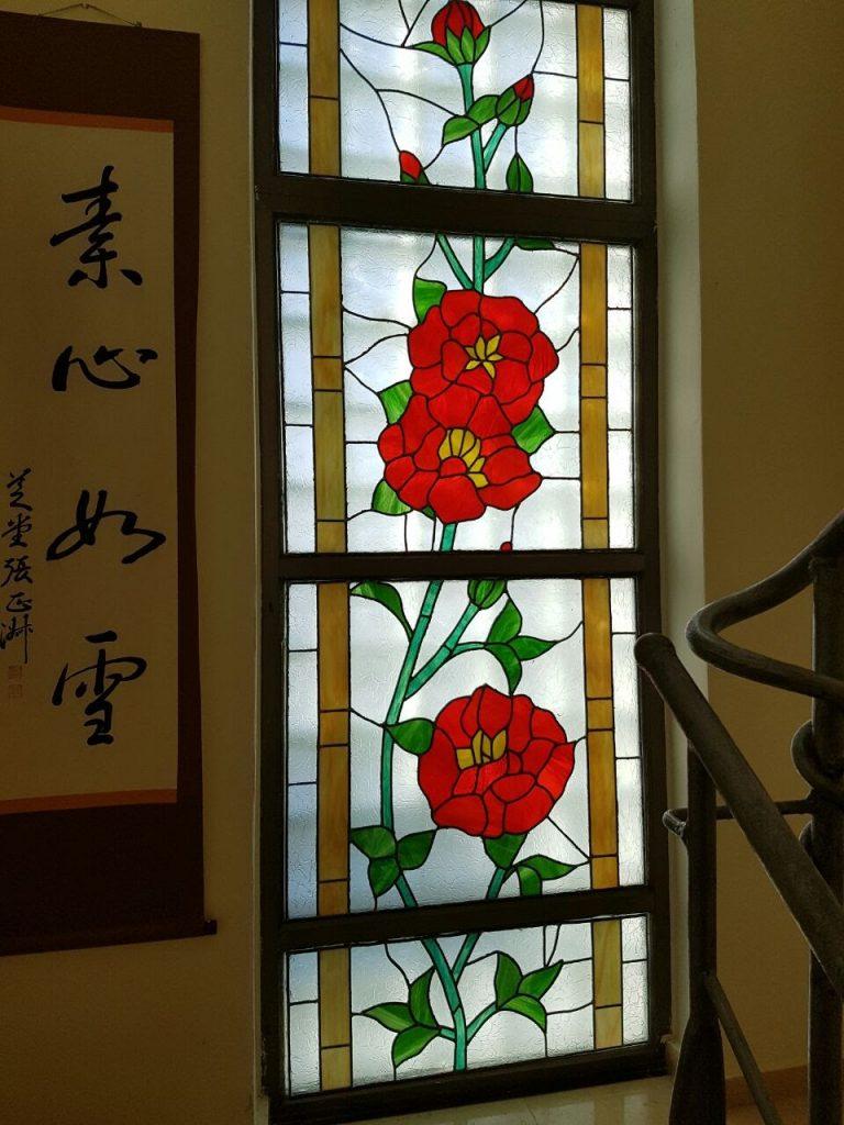 ויטראז עם פרחים אדומים בחלון2016